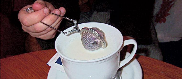 Чашка молока и ситечко для заварки чая