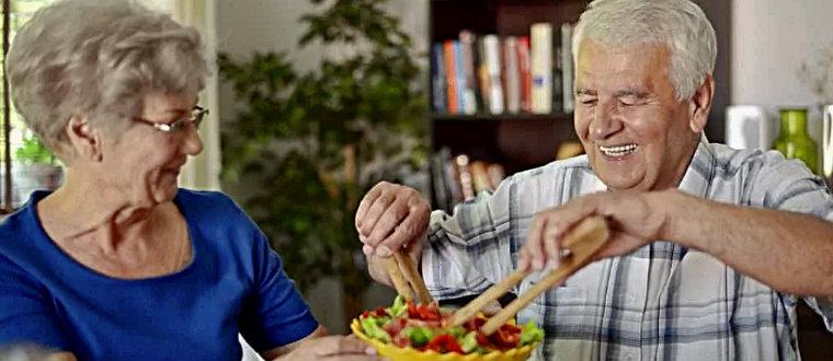 Пожилые люди едят салат
